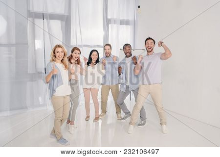Happy Multiethnic Mid Adult People Triumphing And Smiling At Camera