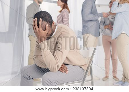 Upset African American Man Sitting On Chair While People Standing Behind During Group Therapy