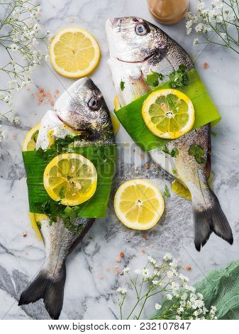 Raw Dorada Fish Prepared To Be Cooked With Lemon, Parsley And Leek On Marble Board