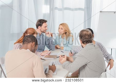 Multiethnic Group Of People Working Together And Taking Notes While Having Conversation