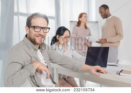 Handsome Mature Man In Eyeglasses Smiling At Camera While Multiethnic People With Laptop And Papers