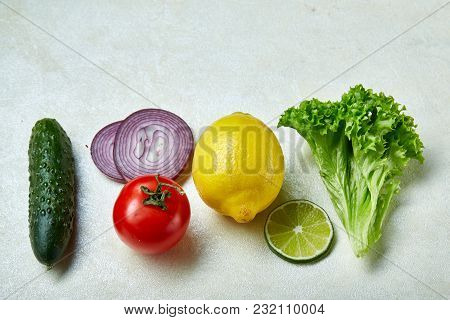 Fresh Vegetables Still Life. Cucumber, Tomato, Onion, Lemon, Lime And Lettuce Lined Up On A White Ba