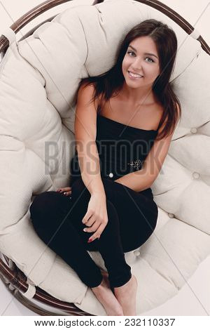 smiling young woman resting in big soft armchair