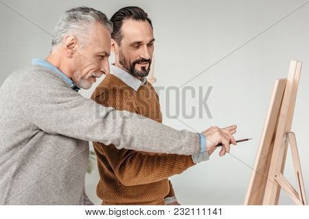 Side View Of Two Male Artists Looking At Easel During Art Class