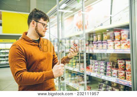 Man Takes Yogurt From Fridge. Grocery Shopping Concept