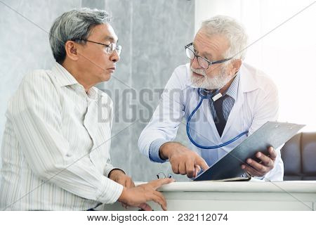 Senior Male Doctor Is Discussing With Male Patient In The Medical Room.