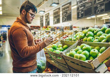 Man Choose Apples At Market. Shopping Concept