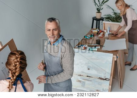 High Angle View Of Senior Man Smiling At Camera While Painting At Art Class For Adults