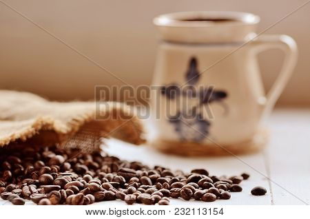 Close-up Of Spilled Coffee Beans From Canvas Sack And Ceramic Mug In Background