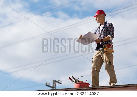 Engineer standing on rooftop looking away and holding blueprint project. Mature construction worker kit standing with copy space. Workman inspecting construction site with sheet of paper in hand.
