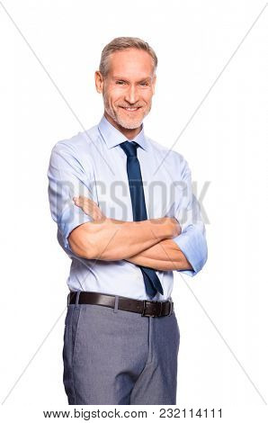 Portrait of successful mature businessman looking at camera isolated on white background. Cheerful senior business man standing with crossed arms. Portrait of smiling manager in formal.