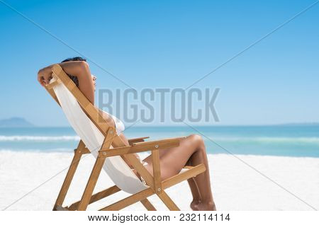 Beautiful young woman in white bikini lying on a deckchair while sunbathing. Woman relaxing on a deck chair at the seaside. Tanned girl relaxing at the tropical beach.