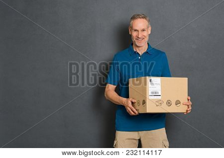 Happy courier holding cardboard box and looking at camera. Smiling delivery man carrying a card box isolated on grey background. Portrait of deliveryman holding parcel with copy space isolated.