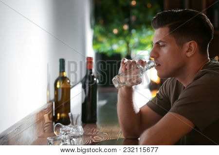 Young man with bottle of drink in bar. Alcoholism problem