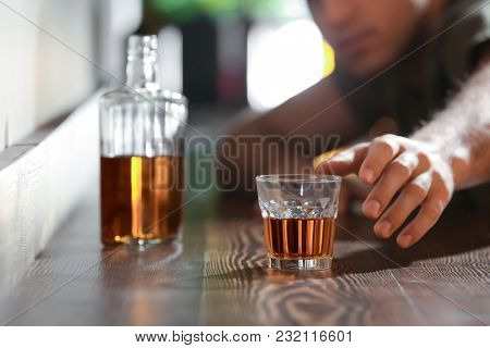 Man reaching for glass of drink in bar. Alcoholism problem
