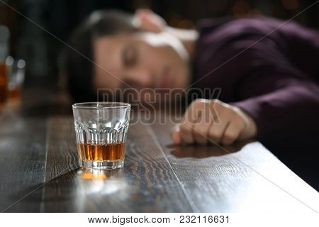 Unconscious drunk man with glass of alcohol in bar. Alcoholism problem