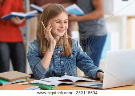 Teenage girl doing homework at table