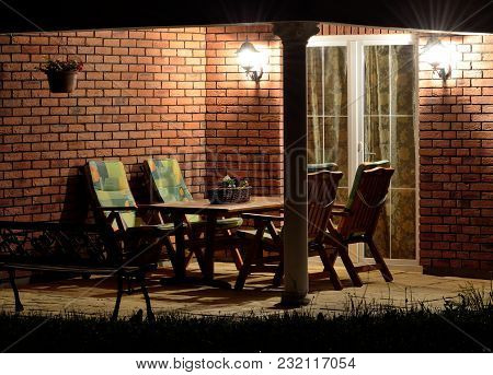 Modern House Garden Terrace Patio Lined With Bricks With Garden Furniture At Night Lighting By Lamps