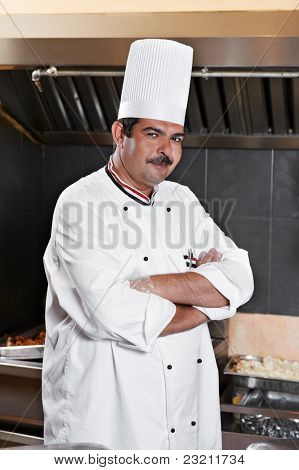 cheerful arab chef man in uniform standing at kitchen