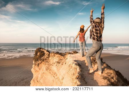 Two best friends near the coastline having fun with arms open