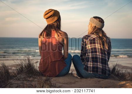 Two best friends sitting on the coastline having a good time