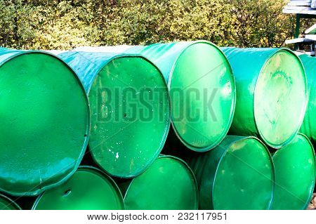 Green Oil Drums Stacked On Top Of Each Other With Plants In The Background. Perfect Image To Show Gr