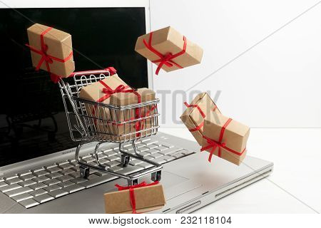 Paper Boxes In A Shopping Cart On A Laptop Keyboard. Ideas About E-commerce, A Transaction Of Buying
