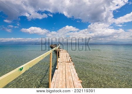 Wooden Pier On Apraos Beach Near Kassiopi Town With Perfect Views Of The Albanian Mountains. Corfu I