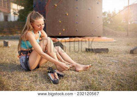 Young Pretty Woman Having A Trauma With Knee After Climbing Practice On Rock Wall. Female Climber Ru