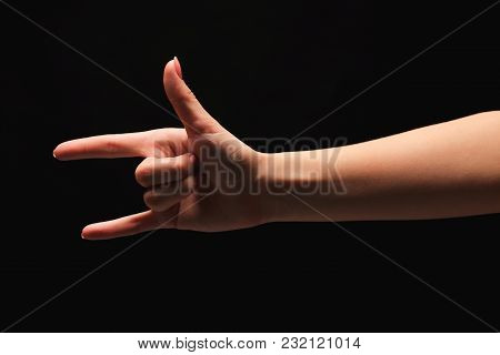 Female Hand Showing Rock Gesture Or I Love U Sign In Hand Language On Black Isolated Background. Cut