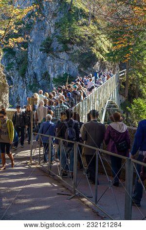 Bavaria, Germany - October 15, 2017: Tourists Stand On Marienbruecke (marie's Bridge)