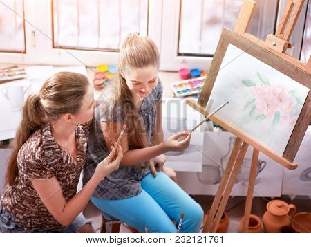 Artist painting easel in studio. Authentic children girl paints with set palette watercolor paints in morning sunlight . Top view school indoor interior handmade crafts . Older sister helps younger.