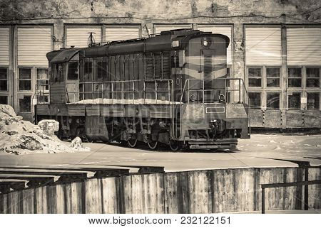 Alone Soviet Old Train In Winter Against The Background Of The Railway Depot Hangars And Rails.