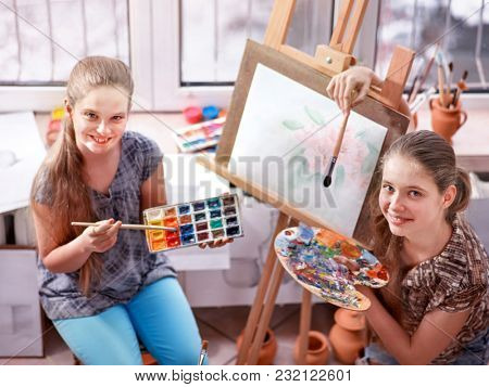 Artist painting easel in studio. Authentic children girl paints with set palette watercolor paints palette in morning sunlight . School interior handmade crafts . Children make gift for holiday.
