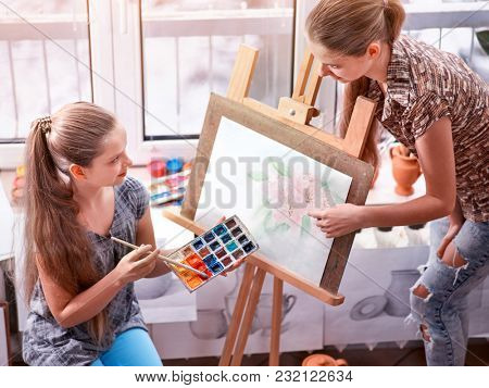 Artist painting easel in studio. Authentic children girl paints with set palette watercolor paints palette and brush in morning sunlight . Training of premior juniors. Diffuse natural light photo.