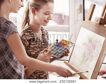 Artist painting easel in studio. Authentic children girl paints with set palette watercolor paints morning sunlight. Discounts on goods for artists. Older sister helps younger. Pupils of art school.