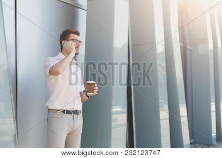 Attractive Thoughtful Businessman Or Lawyer In Eyeglasses Is Talking On Cell Phone And Drinking Coff
