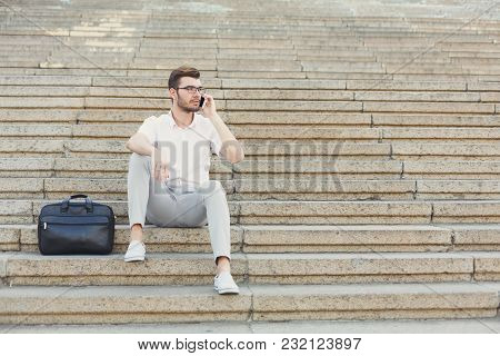 Attractive Thoughtful Businessman Is Talking On Mobile Phone And Sitting On Stone Stairs Next To His
