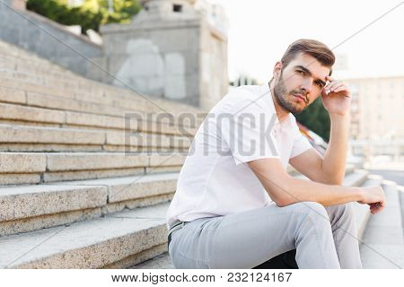 Pensive Businessman Is Pondering Over New Ideas While Sitting On Stone Stairs And Holding His Head,