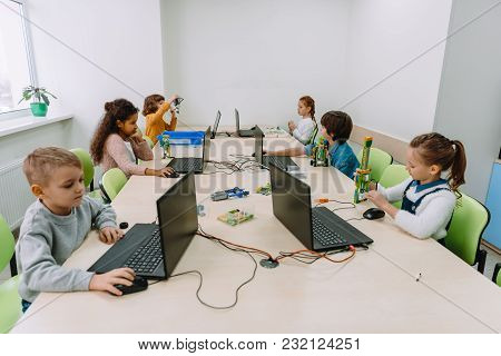 Group Of Focused Kids Working With Computers On Machinery Class