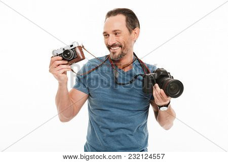 Image of happy handsome mature man photographer standing isolated over white background. Looking aside holding two different cameras.