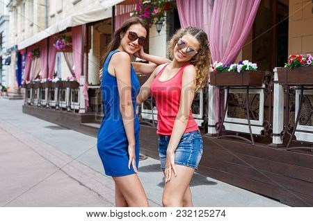 Outdoors Portrait Of Two Female Friends. Girls In Casual Outfits Having A Walk In The City, Having F