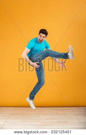 Full length portrait of a crazy young man jumping while celebrating over yellow background