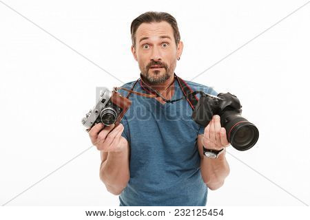 Image of shocked mature man photographer standing isolated over white background. Looking camera holding two different cameras.