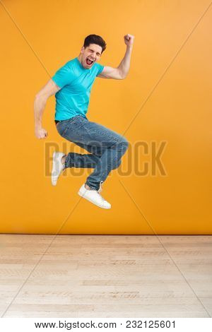 Full length portrait of a happy young man jumping while celebrating over yellow background
