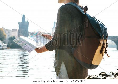 A Young Beautiful Girl Stands And Looks At The Map Next To The Vltava River With The Amazing Old Arc