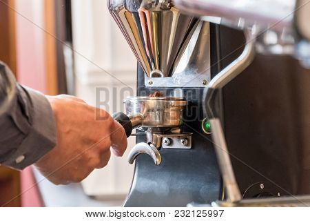 Barista Holding Portafilter In Hand And Grinding Coffee Beans With Grinder To Making Espresso Or Cap