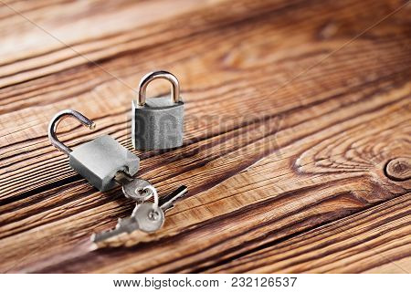 Metal Padlock With Silvered Keys On Old Wooden Background. Estate And Security Concept With Symbol O