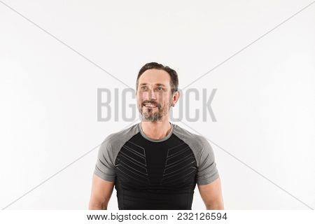 Portrait of masculine man 30s wearing sportswear looking upward on copyspace with smile and satisfied look after doing sports isolated over white background