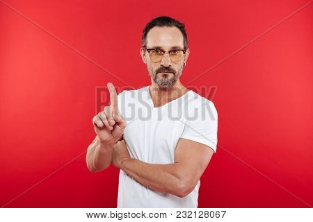 Image of an adult concentrated man in colorful sunglasses standing isolated over red background looking camera make stop gesture.
